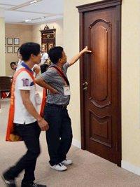 Photo: Visitors examine a wooden door.
