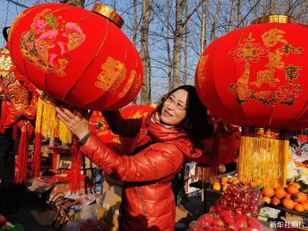 照片:青岛市泊里大集上市民在挑选春节装饰。(新华社)