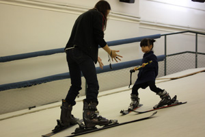 Kids learn to ski under instruction at Slope Infinity indoor snow deck