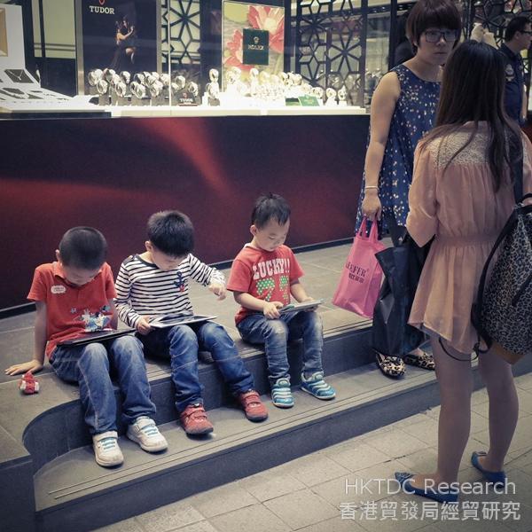 相片:孩子在街上玩平板电脑的游戏