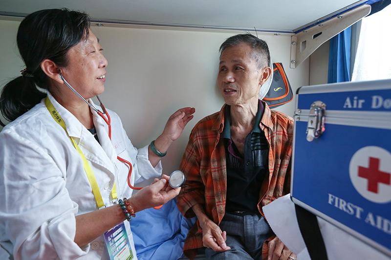 相片:南方快车上的医务人员为旅客检查身体